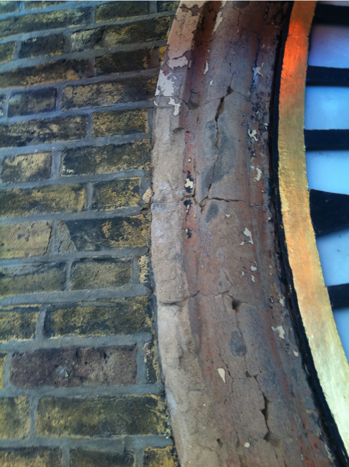 A close up showing the state of the surround to the clock face prior to restoration